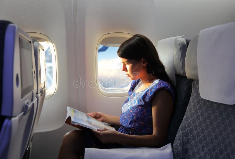 少妇在飞行期间的读书杂志 免版税库存图片