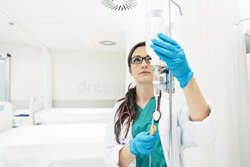少妇在绿色褂子打扮的医生麻醉学者,投入 免版税库存图片