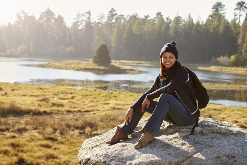 少妇坐一个岩石在看对照相机的乡下 免版税库存图片