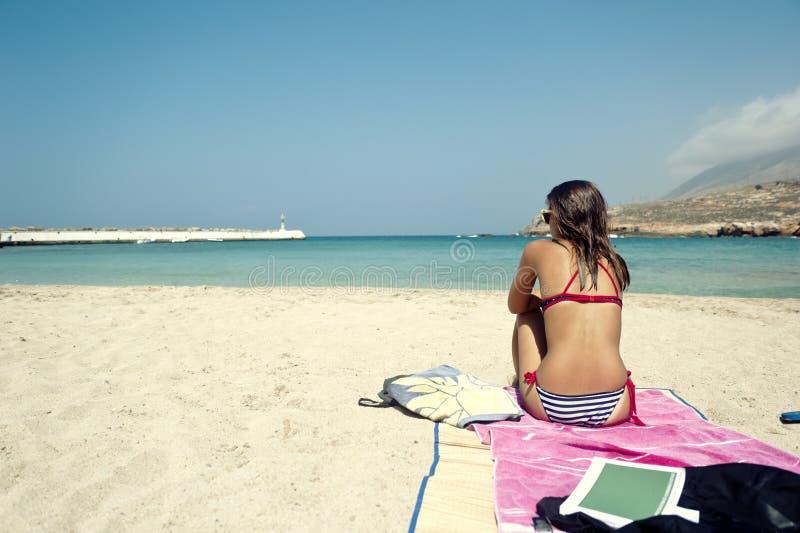 少妇坐一个美丽的海滩 免版税库存图片