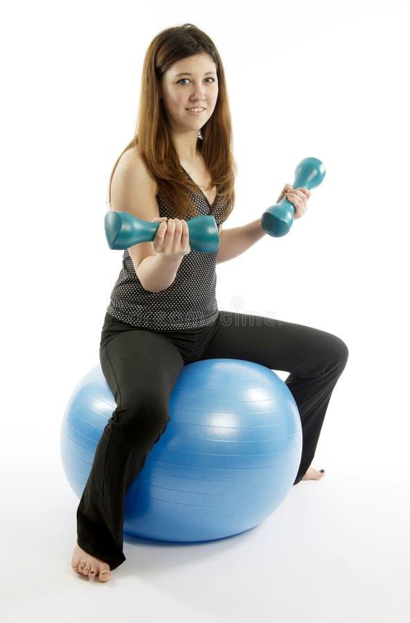 少妇坐与哑铃重量的蓝色执行球 库存图片