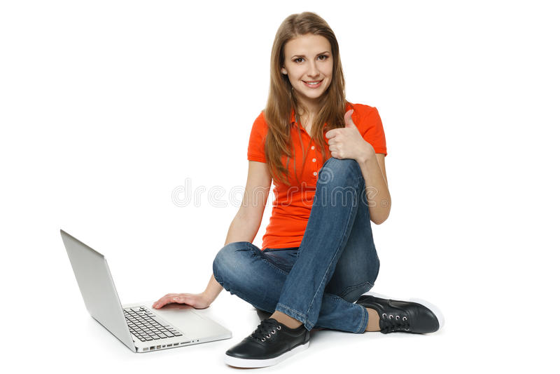 妇女坐与她的做赞许的膝上型计算机的地板 免版税库存照片