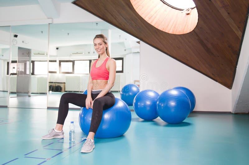 少妇坐在健身房的pilates球 图库摄影