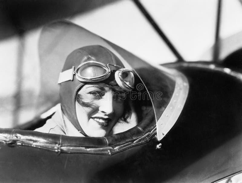 少妇坐在有帽子的一架双翼飞机的和漱口药(所有人被描述不更长生存,并且庄园不存在 供应商 免版税库存图片