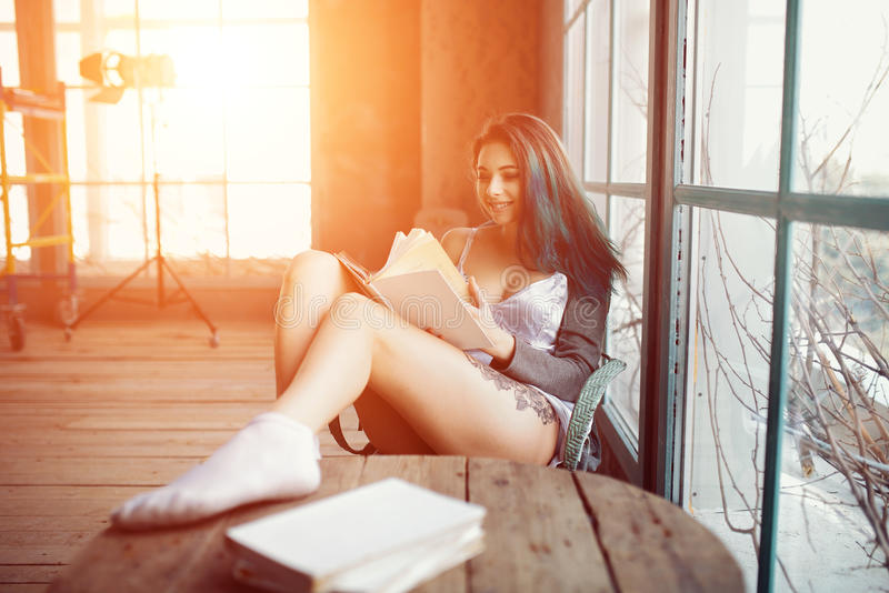 少妇坐在窗口附近的阅读书 免版税库存照片