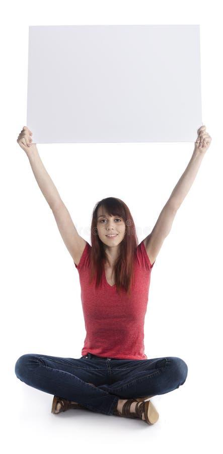 少妇坐培养纸板的地板 库存图片