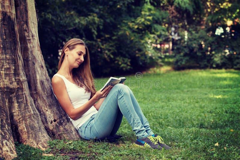 少和少妇_少妇坐室外的草和的阅读书. 阳光, 读取.