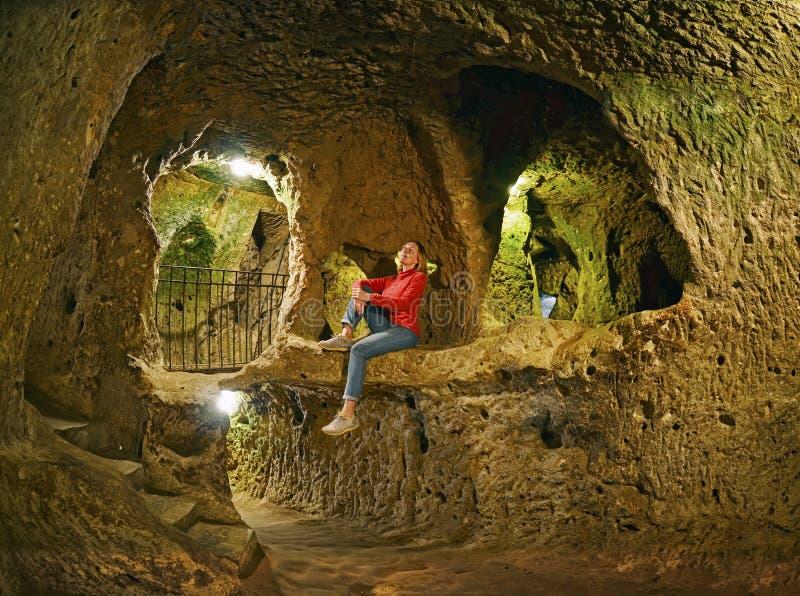 少妇坐岩石 代林库尤洞地下城市 免版税库存图片