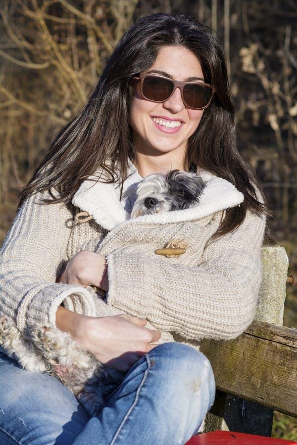 少妇坐拥抱她的狗的长凳 免版税库存照片