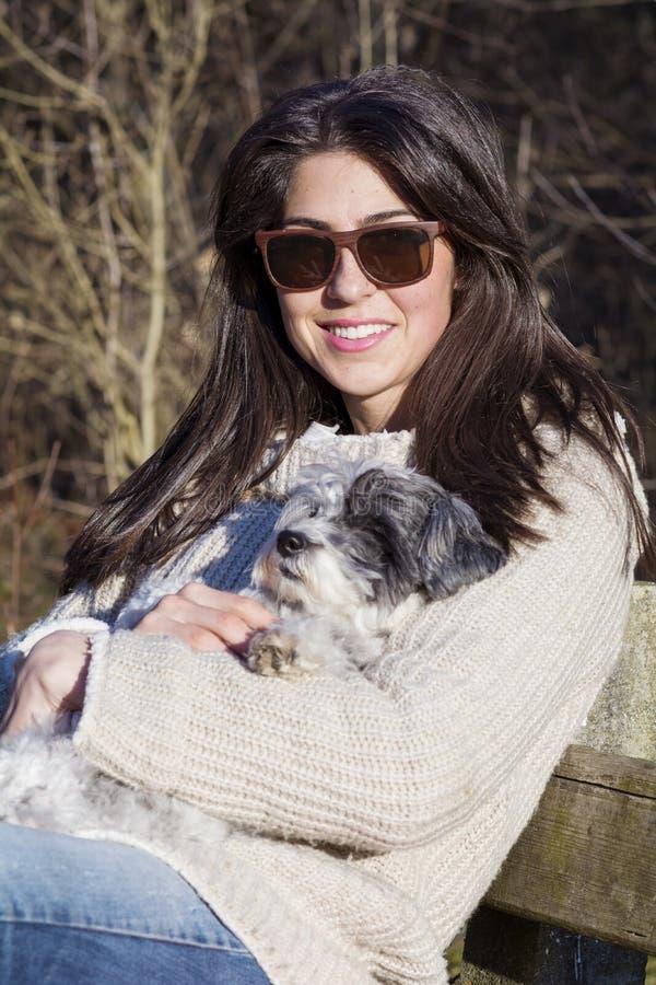 少妇坐拥抱她的狗的长凳 免版税图库摄影