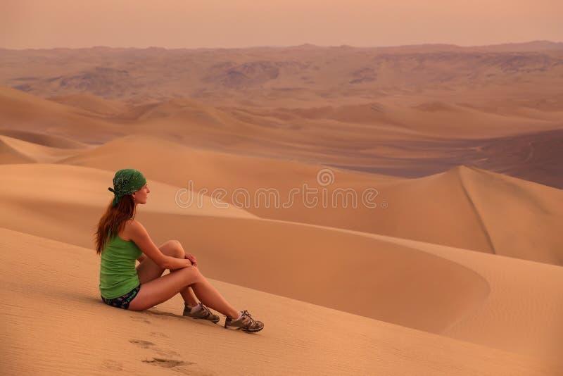 少妇坐沙子在沙漠在Huacachina附近, Ica reg 免版税库存照片