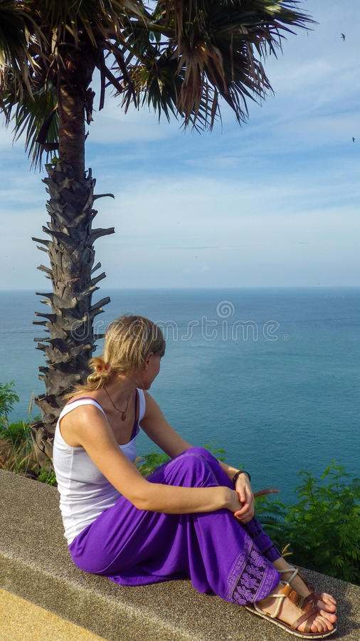 少妇坐海滨在棕榈和观看的海边下 免版税库存图片
