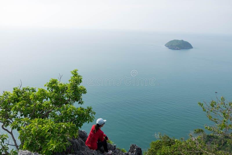少妇坐看对充满感觉的海的峭壁和她 免版税库存照片
