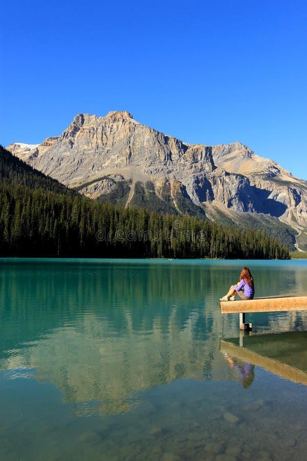 少妇坐码头在鲜绿色湖, Yoho国民同水准 库存图片