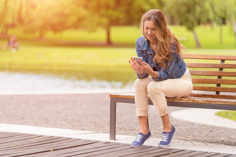 少妇坐长凳和在公园使用她的电话 免版税库存图片