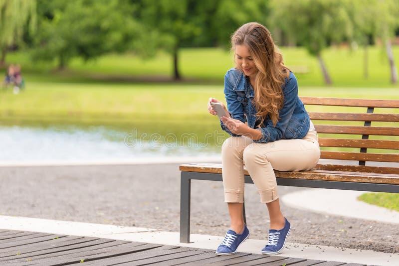 少妇坐长凳和在公园使用她的电话 库存图片