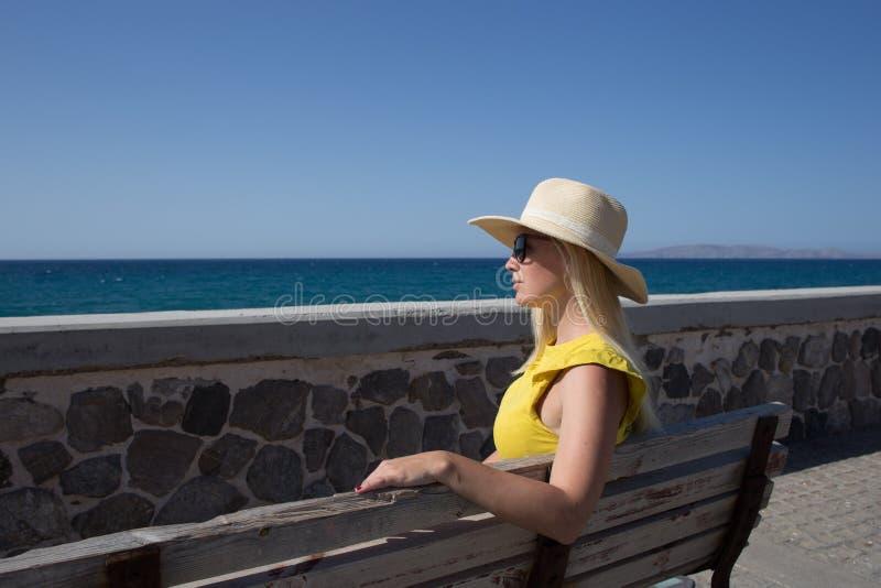 少妇基于一个长木凳的沿海岸区的黄色T恤杉和帽子 免版税库存图片