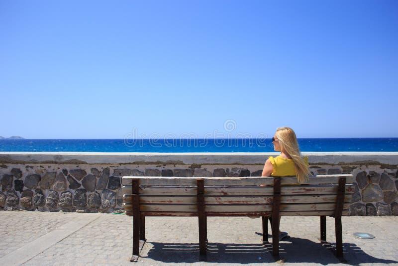 少妇基于一个长木凳的沿海岸区的黄色T恤杉 库存图片