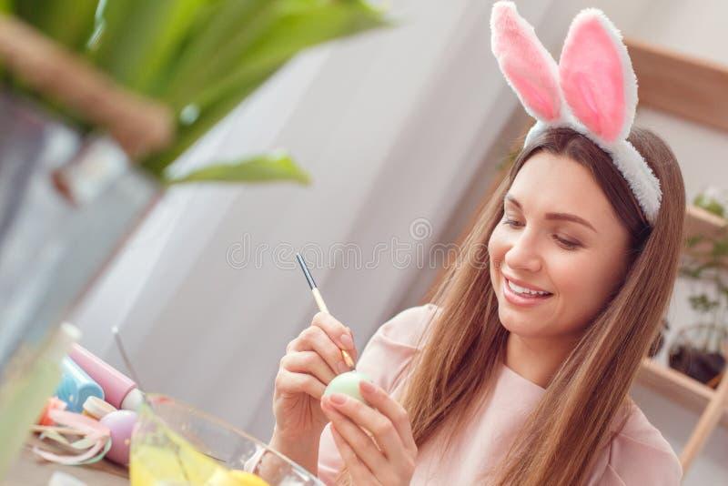 少妇复活节在坐着色的兔宝宝耳朵的celbration概念在家怂恿绘画小点 免版税库存照片