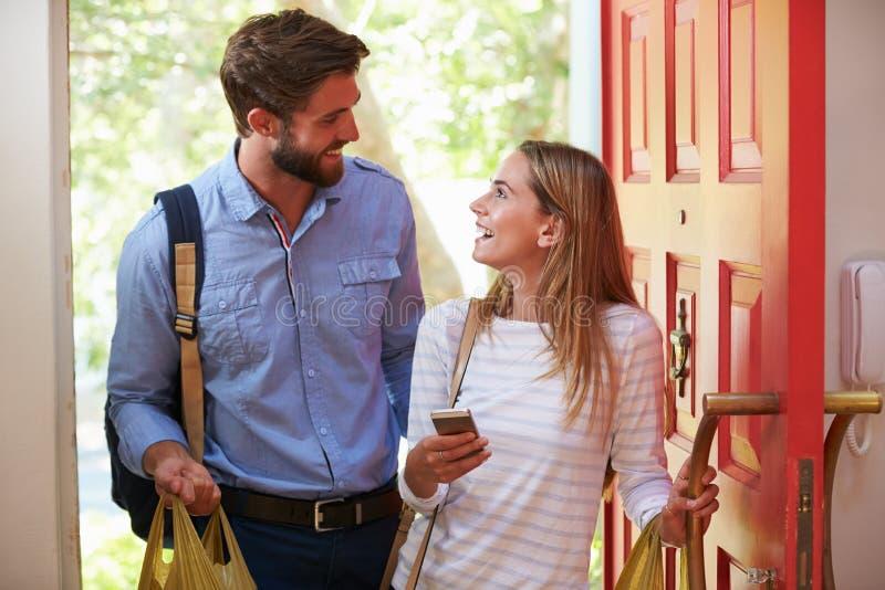 少妇夫妇为回家与购物一起使用 库存图片