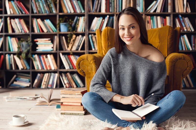 少妇学生在坐的图书馆里在家看快乐的照相机 库存照片