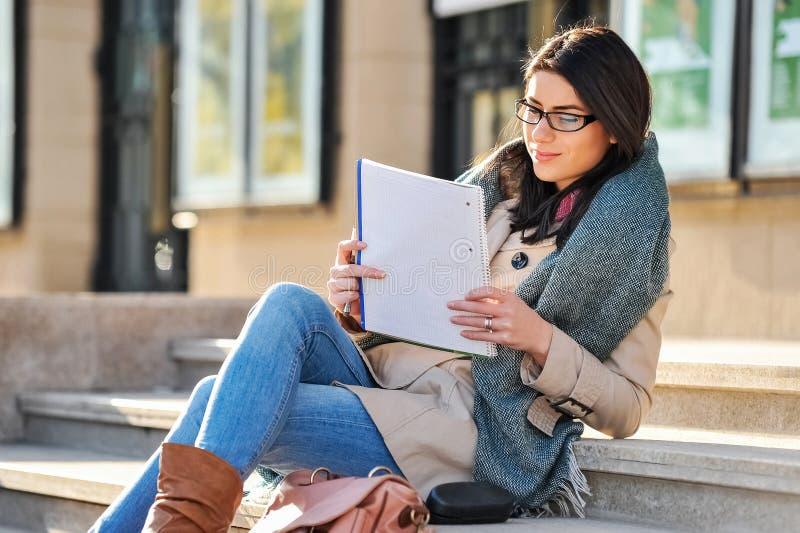 少妇学生读室外 免版税库存图片