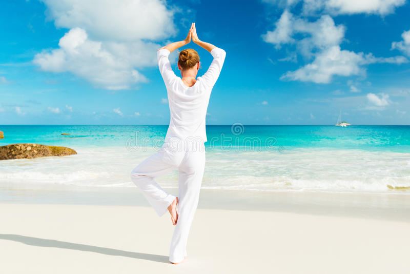 少妇实践在海滩的瑜伽 免版税库存照片
