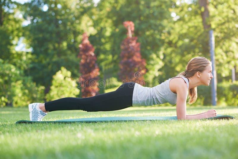 少妇实践的瑜伽户外在公园 免版税库存照片