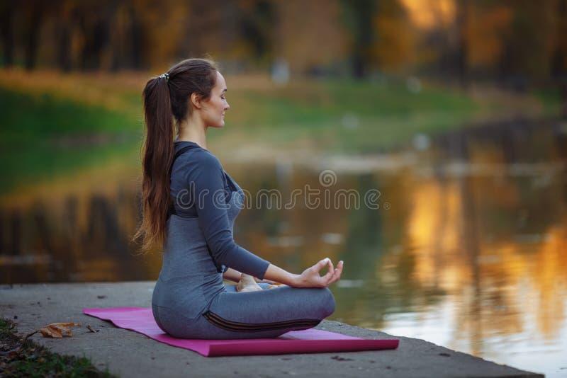 少妇实践的瑜伽户外 女性思考美好的秋天自然室外infront  免版税库存照片