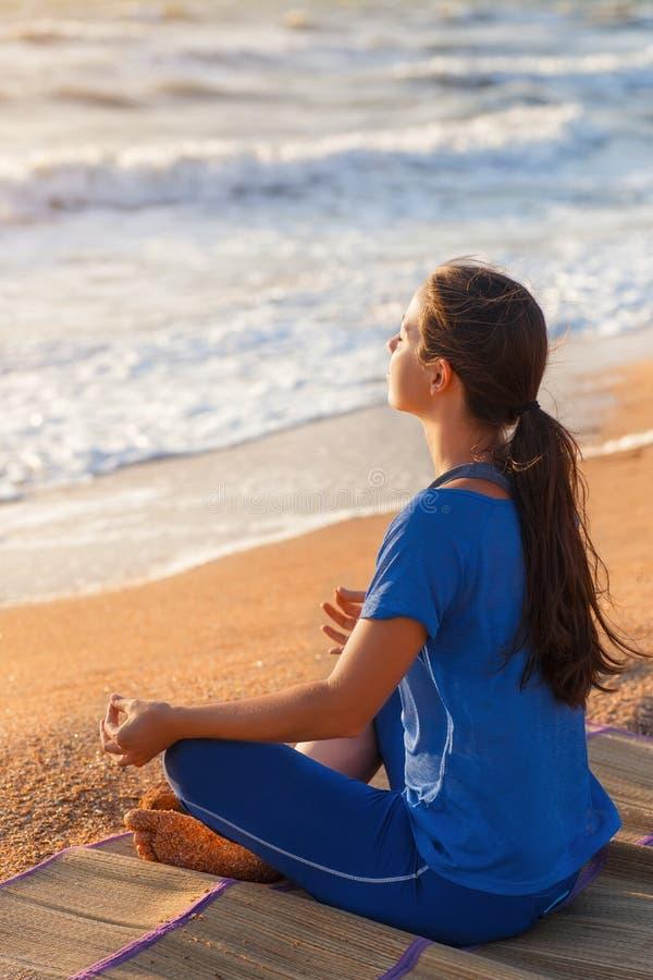 少妇实践的瑜伽户外 免版税库存照片