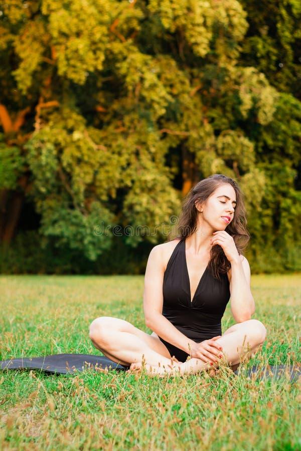 少妇实践的瑜伽本质上 坐绿草 免版税库存图片