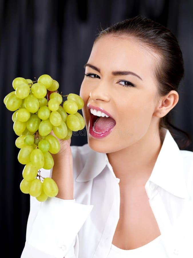 少妇对叮咬到一束葡萄里 库存图片