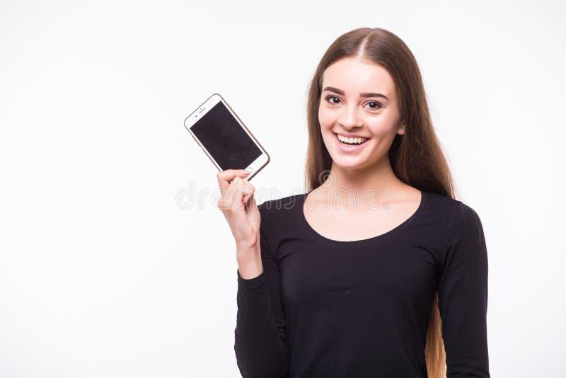 少妇展示显示有黑屏幕的流动手机和微笑在白色背景 免版税库存照片