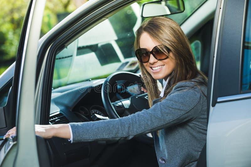 少妇开头车门 免版税库存图片