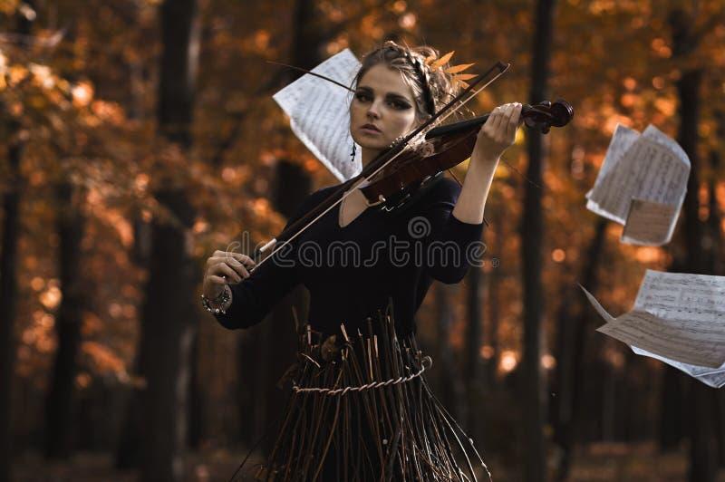 少妇弹在音乐飞行笔记的小提琴 免版税库存图片
