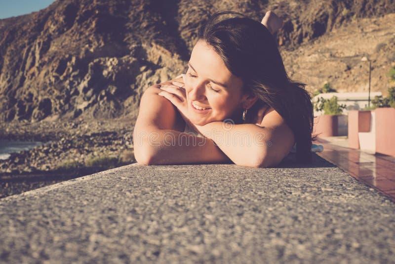 少妇微笑和在墙壁上放下在vacat的海滩附近 免版税库存照片