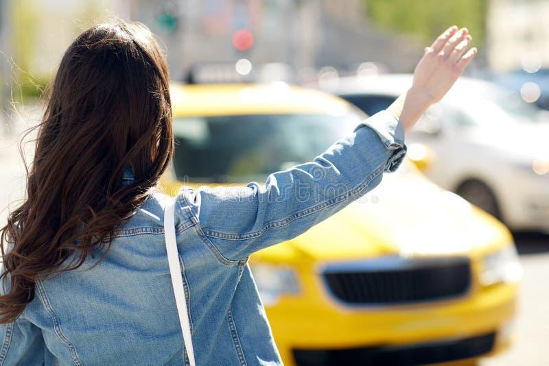 少妇或女孩传染性的出租汽车在城市街道上 库存图片