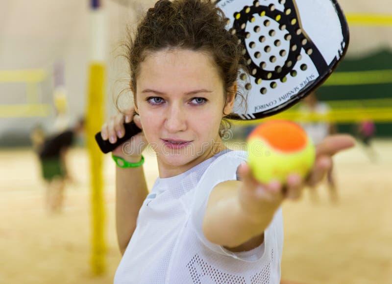 少妇打在报道的法院的海滩网球 免版税库存图片