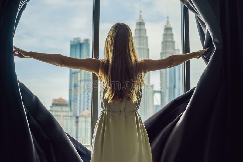 少妇打开窗帘和神色在skyscrape 免版税库存照片