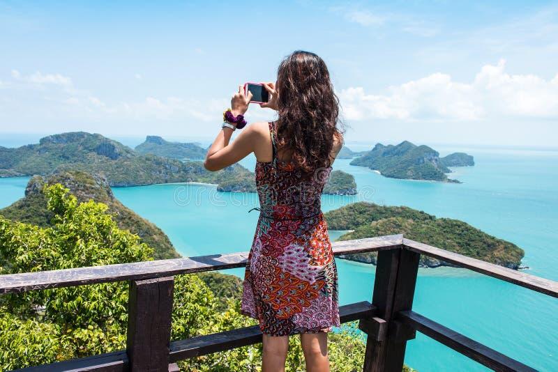 少妇拍与智能手机的照片 免版税图库摄影