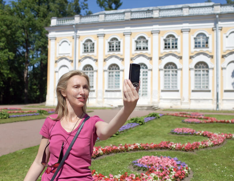 少妇拍摄自己在手机反对亭子石头大厅在Oranienbaum,彼得斯堡,俄罗斯 免版税库存照片