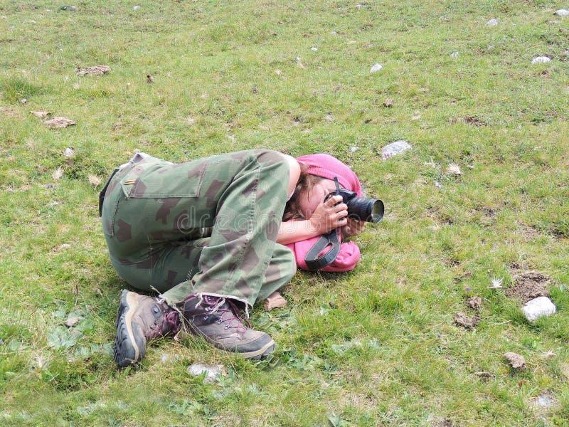 少妇拍放置草甸的照片 免版税图库摄影