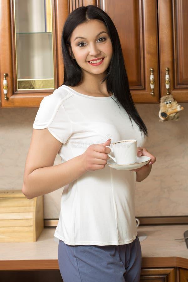 少妇拿着一个杯子用咖啡或茶反对 免版税库存照片