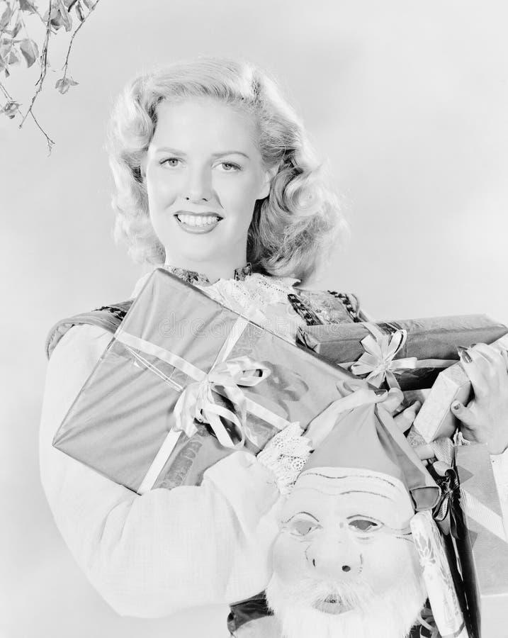 少妇握胳膊的有很多礼物和圣诞老人面具(所有人被描述不是更长的生存和没有庄园exis 免版税图库摄影
