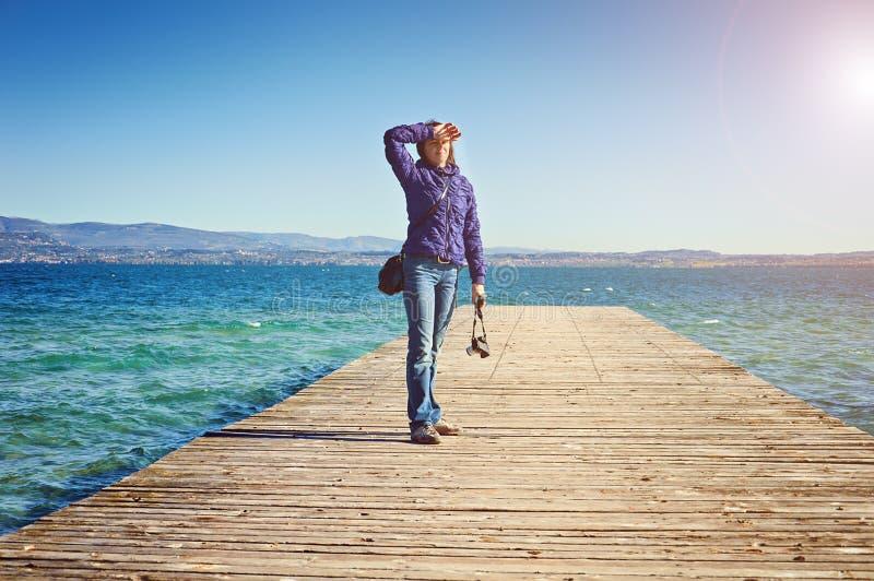 少妇摄影师放光早晨太阳桥梁码头西尔苗内lago di加尔达意大利 免版税库存照片