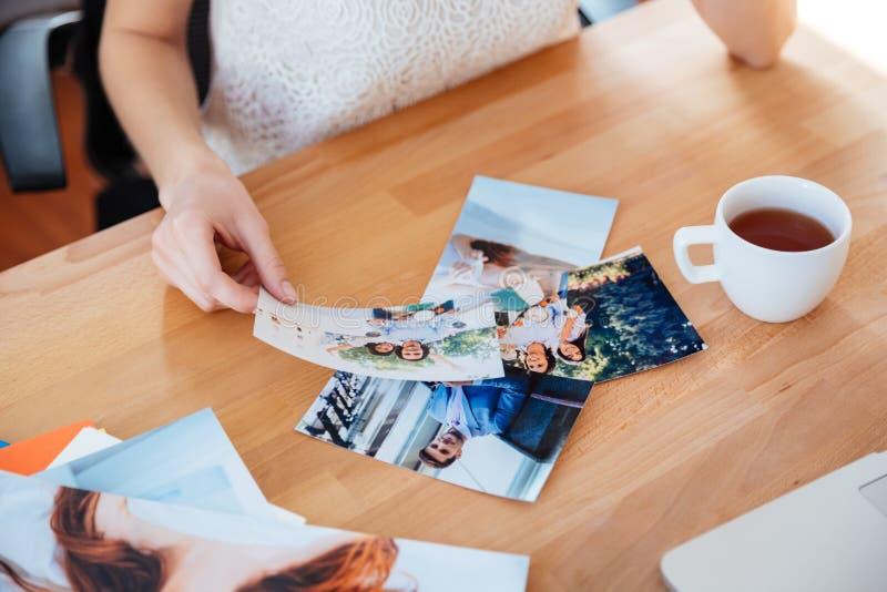 少妇摄影师饮用的茶和选择照片表  免版税库存照片