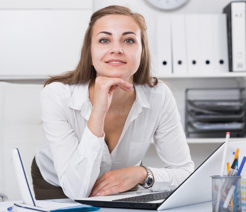 少妇摆在,当工作在膝上型计算机后时 图库摄影