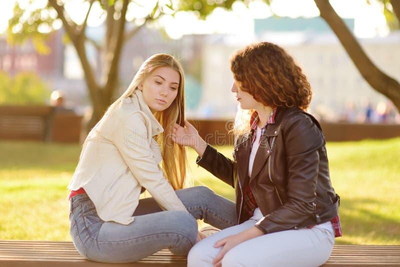少妇支持和安慰她的upsed朋友 两女孩在交谈时 免版税库存照片