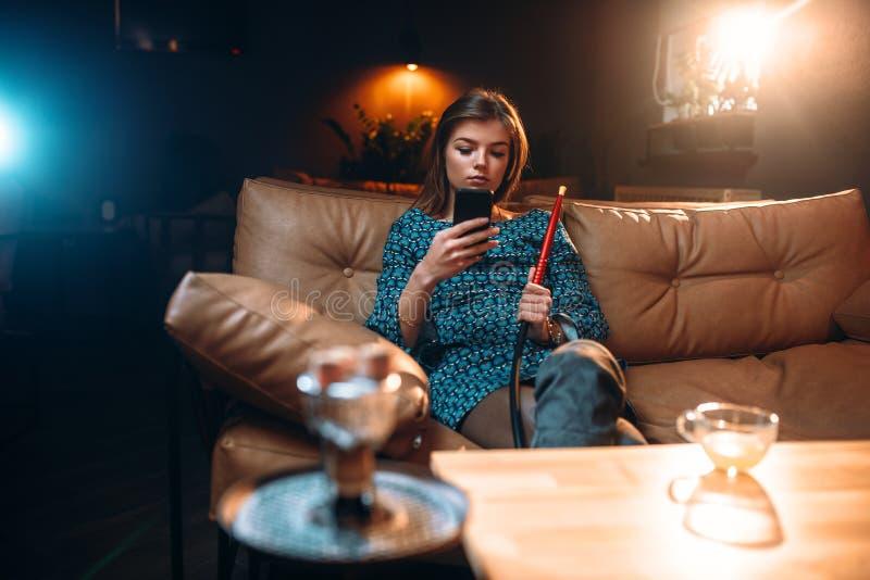少妇放松,在酒吧的抽烟的水烟筒 库存照片