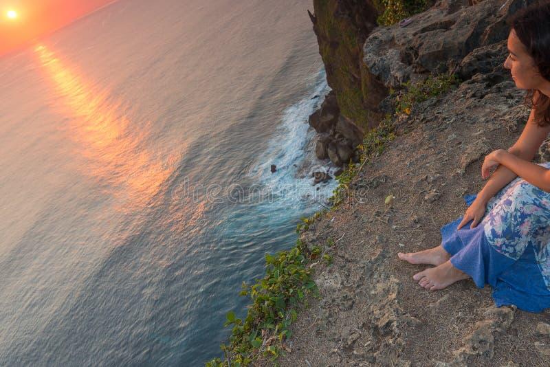 少妇敬佩日落,巴厘岛,印度尼西亚 免版税图库摄影